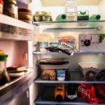 Ein offener Kühlschrank, dessen bunter Inhalt an Lebensmitteln beleuchtet ist