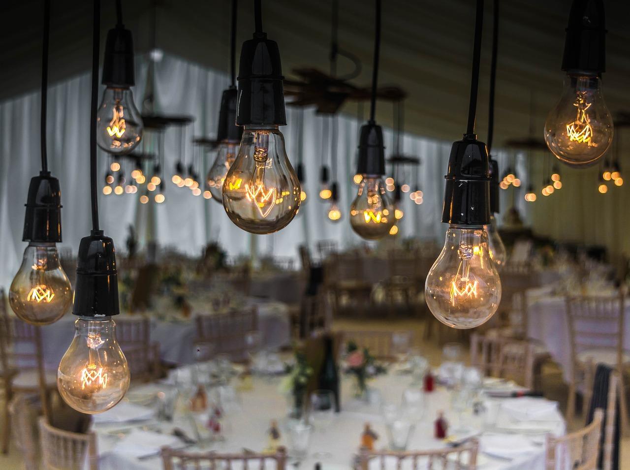 Gelb glühende Glühbirnen hängen von der Decke in einem Saal mit festlich geschmückten Tischen für eine Hochzeit