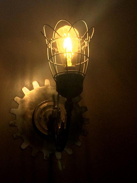 Eine Glühlampe, die gelbes Licht verströmt ist in einem Metallkäfig auf einer Halterung die an einem Zahnrad an der Wand befestigt ist