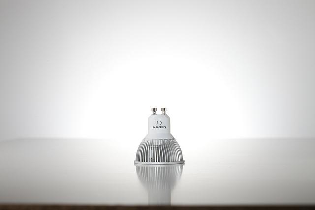Eine Lampe mit einem GU10-Sockel, bei dem man die untere abgerundete Kante sowie die beiden Metallstifte gut sehen kann.