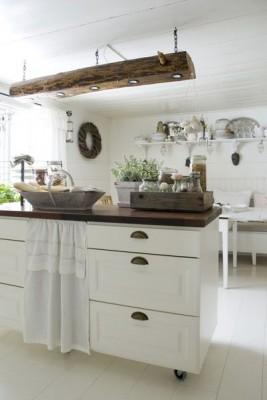 In einem Holzbalken wurden mehrere Spots versenkt und dieser dann aufgehangen. So entstand eine rustikale Küchenleuchte.