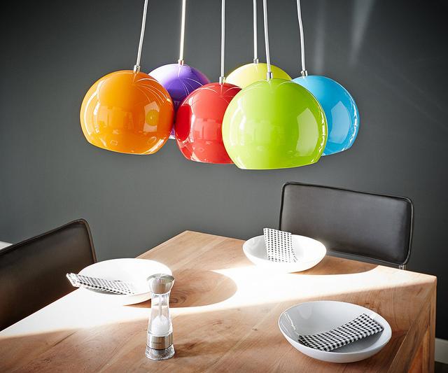 Eine Hängeleuchte mit vielen bunten Lampenschirmen hängt von der Decke über einen gedeckten hölzernen Esstisch.