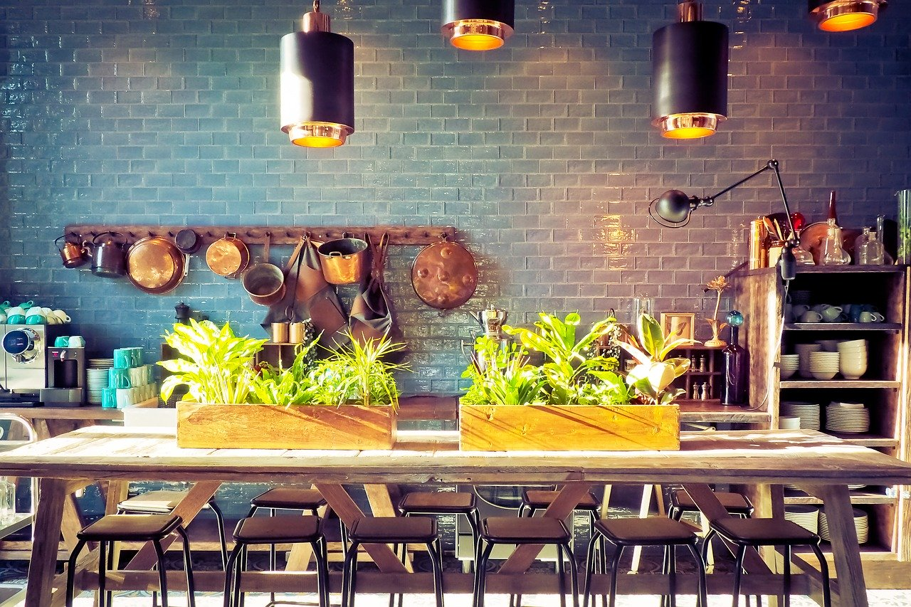 Über einem großen Holztisch hängen einige Küchenleuchten