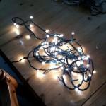 Eine LED-Lichterkette liegt auf dem Fußboden, weil so total verworren und verknotet ist.