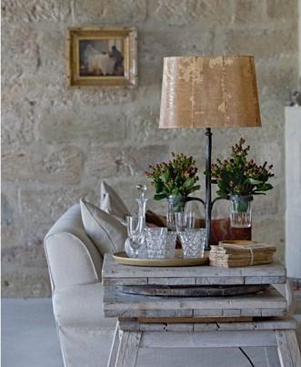 Vor einer Steinwand steht ein helles Sofa und ein Holztisch im Shabby Chic. Dazu wurde eine Stehlampe aus dunklem Metall und einem Lampenschirm in einem Beigeton kombiniert.