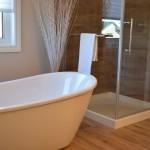 Ein Badezimmer mit einer weißen, freistehenden Wanne und einer gläsernen Dusche daneben. Oberhalb der Badewanne ist ein Fenster. Der Raum ist mit Tageslicht gefüllt.