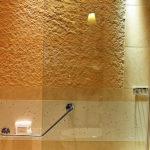 Eine kunstvoll angestrahlte Wand über einer Badewanne mit Glastrennwand