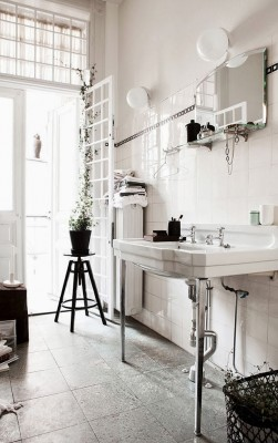 In einem hellen Badezimmer mit einigen verspielten Elementen bilden die schlichten, kugelrunden Spiegellampen einen Hingucker.