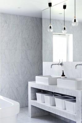 Ein hell gefliestes Bad mit einem eleganten Waschtisch aus Stein, vor den Spiegeln hängen zwei Deckenleuchten.