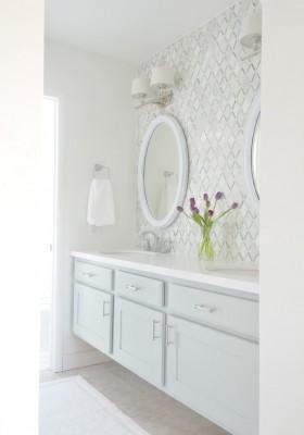 Ein weißer Waschtisch vor einer weiß gefliesten Wand, darüber ein weißer, ovaler Spiegel mit Wandlampen, die weiße Stoffschirme haben. Der einzige Farbklecks ist ein Strauß pinker Tulpen auf dem Waschtisch.