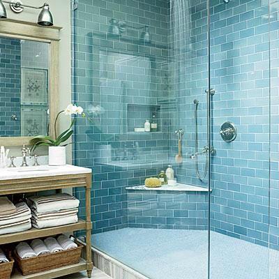 Man sieht eine blau geflieste Wand in einer Duschkabine aus Glas, daneben steht ein hölzerner Waschtisch mit Spiegel, über dem metallische Industrielampen hängen.