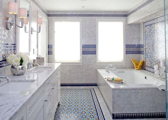 in einem opulenten Badezimmer mit blauen Mosaikfliesen steht links der Waschtisch, rechts die Badewanne. Als Spiegelleuchten beim Waschtbecken dienen zwei Wandleuchten mit rosafarbenen Schirmen.