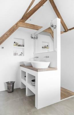 Ein helles Badezimmer mit Holzbalken und einem hölzernen Waschtisch sowie metallischen Armaturen und Spiegelleuchten.