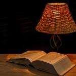Auf einem Tisch liegt ein dickes, aufgeschlagenes Buch, daneben steht eine Tischleuchte mit einem Lampenschirm aus Korbgeflecht. Das Licht ist sehr warm.