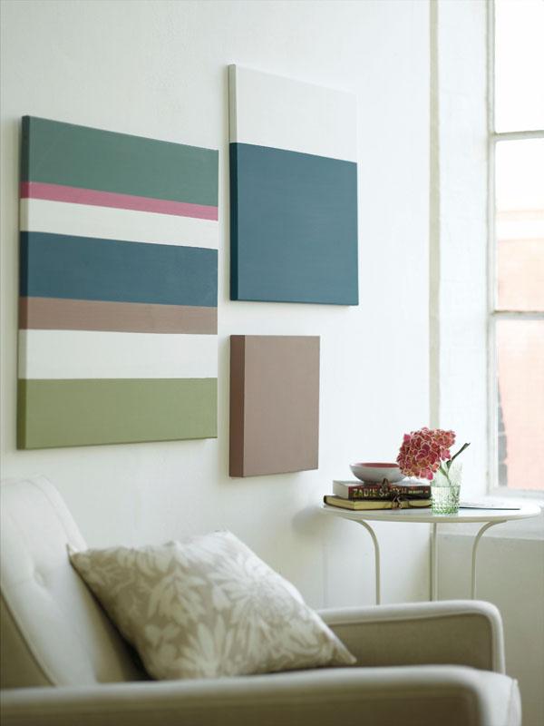 An einer Wand hängen drei verschiedene Leinwandbilder, die Farbflächen in Grün-, Petrol- und Brauntönen zeigen. Darunter steht ein Sessel und ein Beistelltisch, daneben ist ein Fenster.
