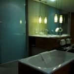 In einem modernen, blau gefliesten Badezimmer hängen zwei Spiegelleuchten von der Decke herab.