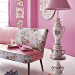 In einem rosafarbenem Wohnzimmer neben einem Sofa mit Rosenstoff steht eine Stehleselampe aus Geschirr.