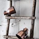 An einer Holzleiter klemmen zwei LED-Klemmleuchten mit braunem Lampenschirm aus Metall.