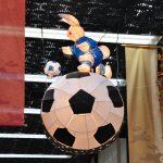 eine lampe bestehend aus einem riesigen fußball hängt von der decke, auf ihr steht ein papierener hase der ebenfalls einem fußball hinterher läuft