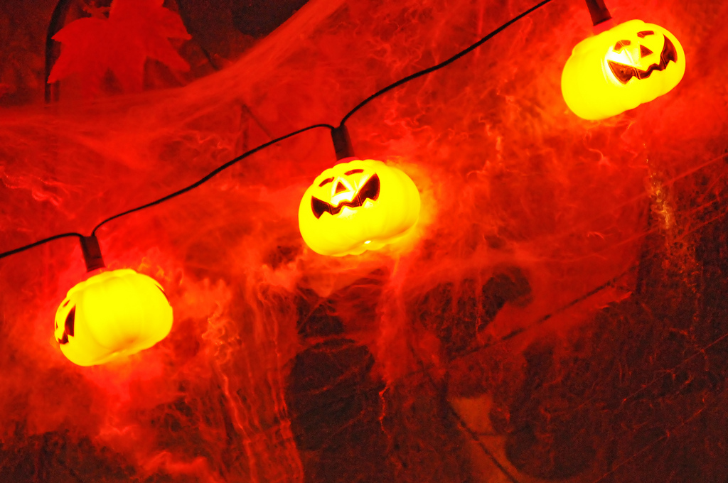Eine Lichterkette aus kleinen Kürbissen taucht eine gruselige Halloween-Deko in orangefarbenes Licht.