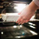 Eine Hand, die einen Auflauf in den Ofen schiebt, während die Backofenlampe leuchtet