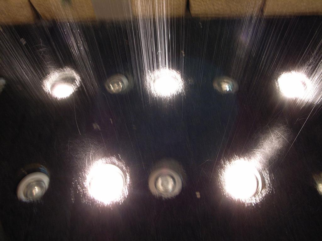 Einbauspots am Boden einer Dusche, während Wasser auf sie fällt - die richtige Beleuchtung für Feuchträume ist wichtig!