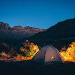 Ein Zelt wird nachts in der freien Natur erleuchtet - wahrscheinlich mit einem Akkustrahler.