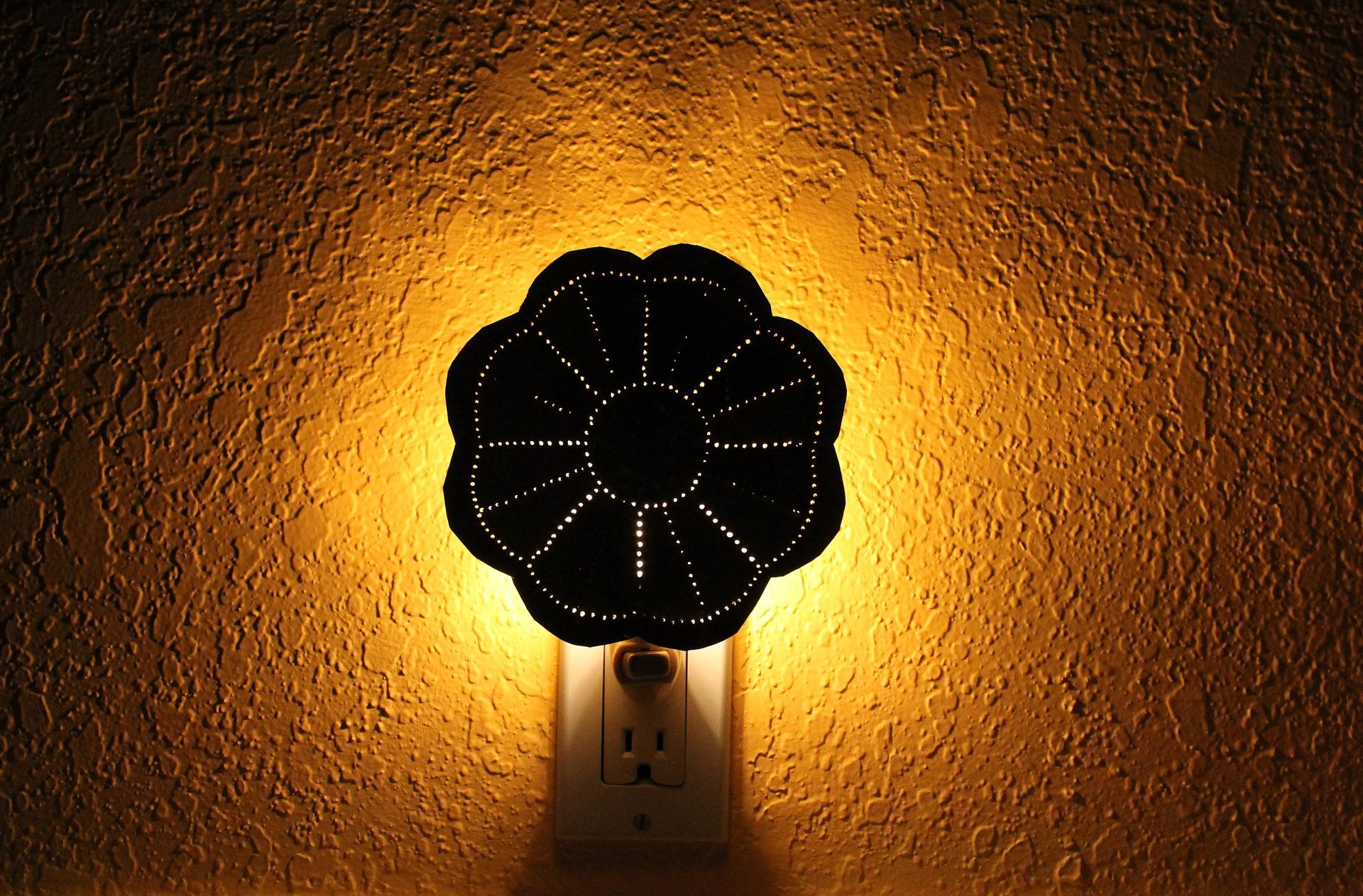 Ein Nachtlicht steckt in der Steckdose und wirft indirektes gelbes Licht auf die Wand.