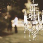 kleiner Kronleuchter mit weißen Kerzenleuchten hängt in einem garten