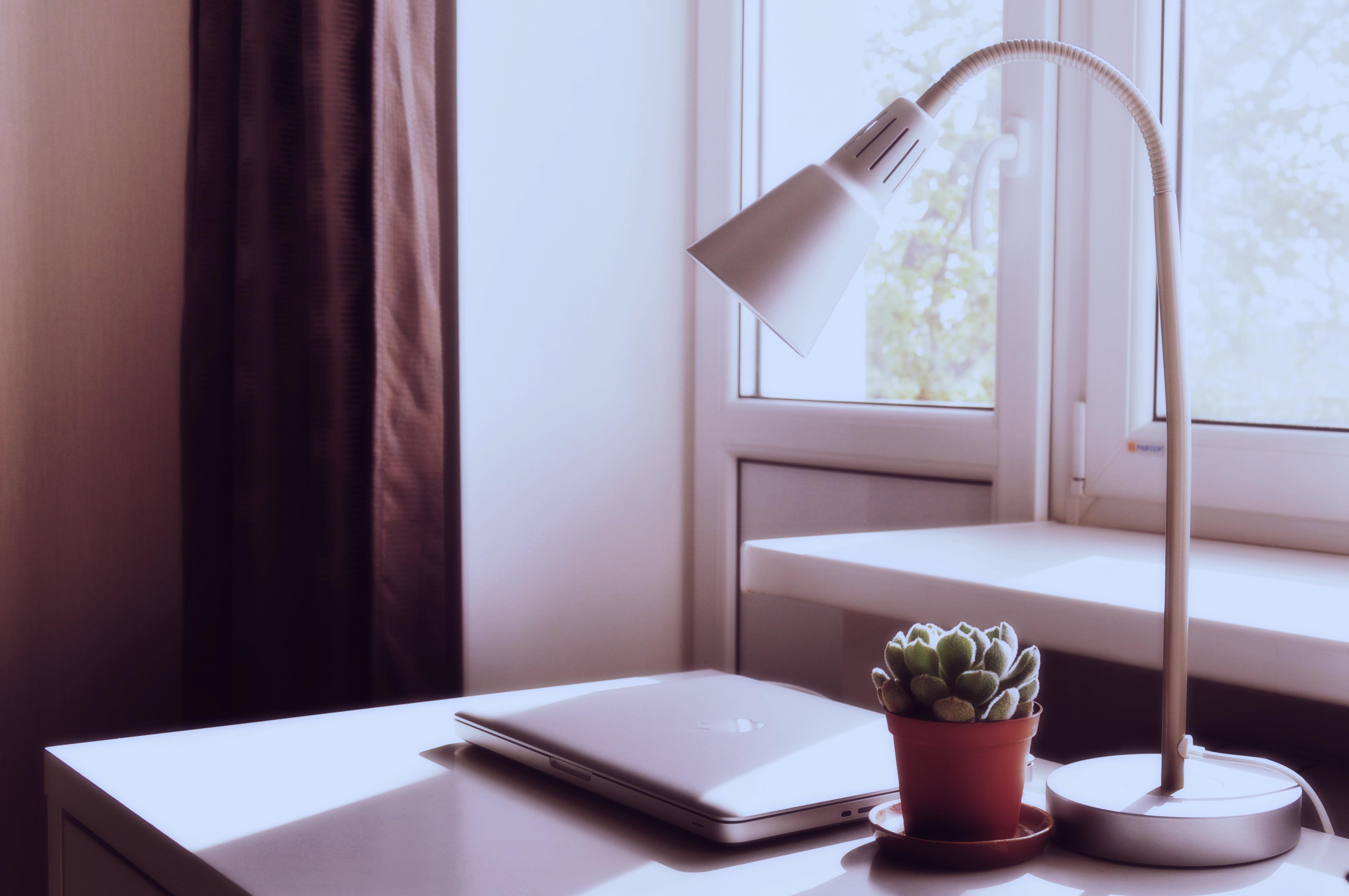 Eine weiße Schreibtischlampe steht vor einem Fenster auf einem Tisch, daneben ein Laptop und eine Pflanze.