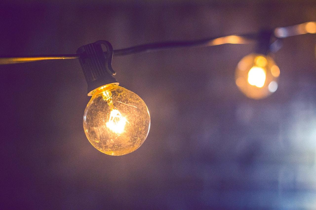 Eine Lichterkette mit größeren Glühlampen hängt in der Dunkelheit - eine tolle Terrassenbeleuchtung!