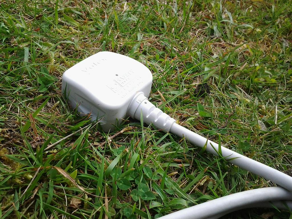 Ein Stecker mit Kabel steckt im Rasen