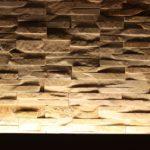 Eine Wand aus Natursteinen in einer Wohnung wird durch indirektes Licht von unten erleuchtet