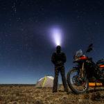 Eine Person steht nachts mit Zelt und Mototrrad in der freien Natur und schaut nach oben, eine Stirnlampe leuchtet in den Himmel