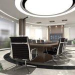 Ein moderner, runder Besprechungsraum wird von einer großen runden Deckenleuchte bzw. Bürolampe sowie von vielen kleineren Strahlern beleuchtet