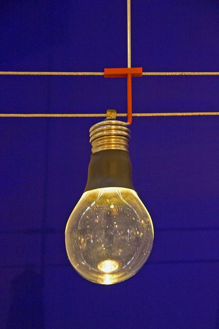 Eine Glühbirne hängt an zwei stromleitenden Seilen