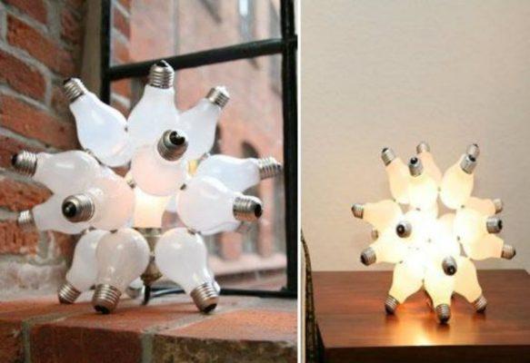 Mehrere alte Glühbirnen sind mittels eines Drahtes oder Heißkleber aneinandergedreht und um eine leuchtende Glühbirne als Lampenschirm platziert.