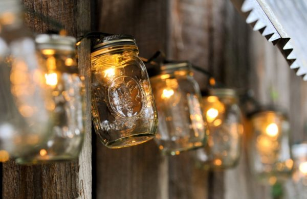Marmeladengläser mit einer leuchtenden Glühbirne drin sind aneinandergereiht an einer Wand aufgehangen.