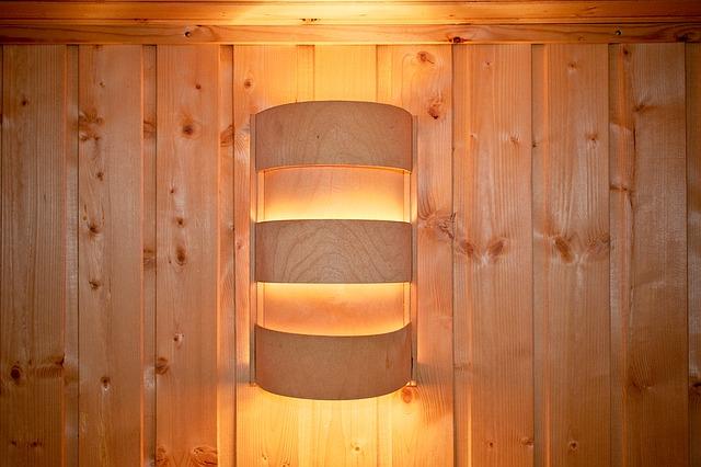 Eine Saunalampe aus gebogenem Holz an der Wand, welche ein angenehmes, indirektes Licht verströmt.