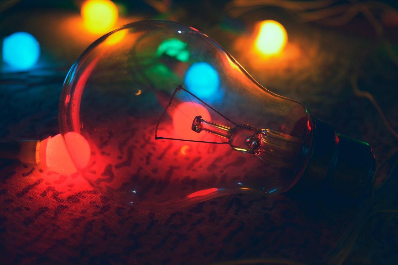 Eine Glühbirne liegt auf dem Boden und wird durch verschiedene kleinere Leuchtmittel bunt beleuchtet