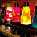 Mehrere Lavalampen leuchten in verschiedenen Farben und stehen in einem Regal
