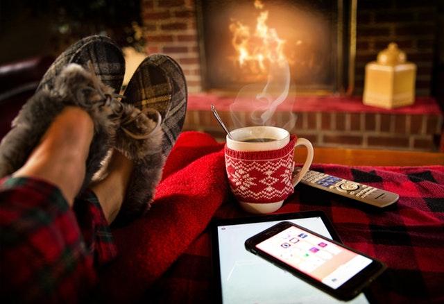Jemand sitzt mit dicken Hausschuhen gemütlich vor dem Kamin und einer Tasse Tee, daneben liegt ein Handy, mit dem man die Helligkeit des Lichtes steuern könnte.