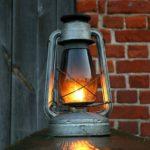 Eine angerußte, brennende Petroleumlampe steht vor einer Scheune auf einem Brett