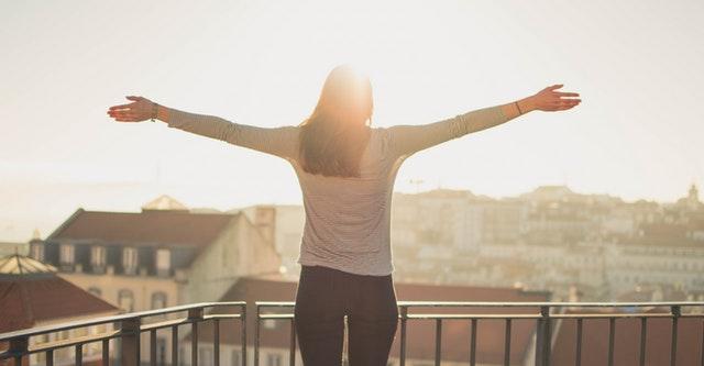 Eine Frau steht mit ausgebreiteten Armen auf einem Balkon und wird von der Sonne beschienen.