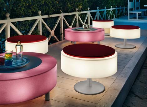 Mehrere verschiedenfarbig leuchtende LED-Möbel stehen auf einer Terrasse