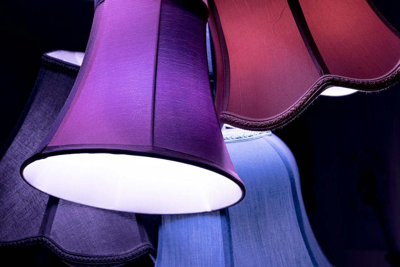 Mehrere, unterschiedlich farbige Lampenschirme in Lila, Blau und Violett leuchten sanft.