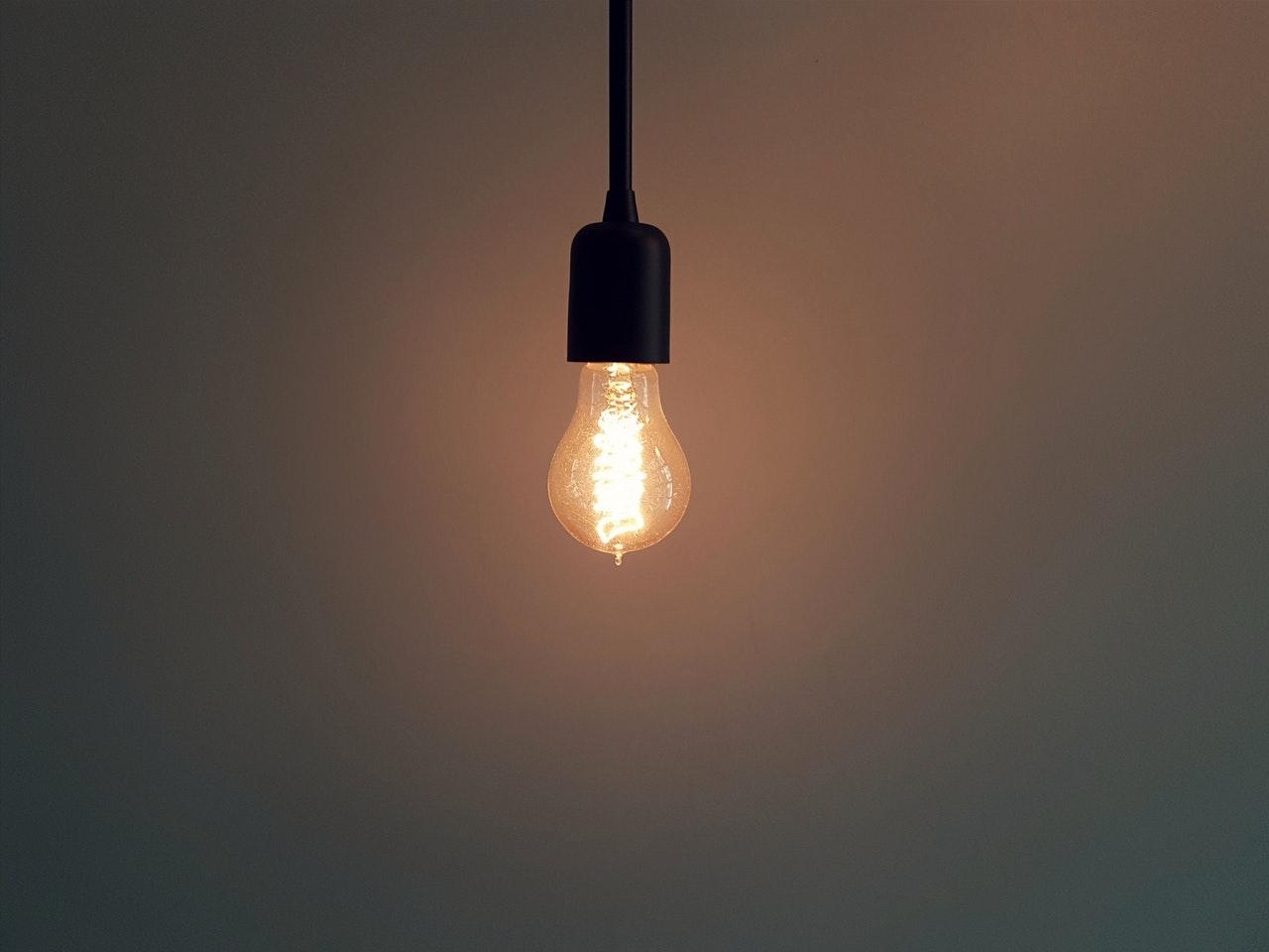 Eine LED-Retrofit Glühlampe in einer schwarzen Fassung hängt leuchtend von oben herab ins Bild.