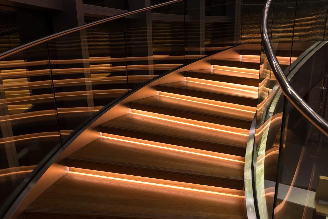Eine sanft geschwungene Treppe in modernem Look führt empor, ihre Stufen sind dank einer Treppenbeleuchtung erhellt.