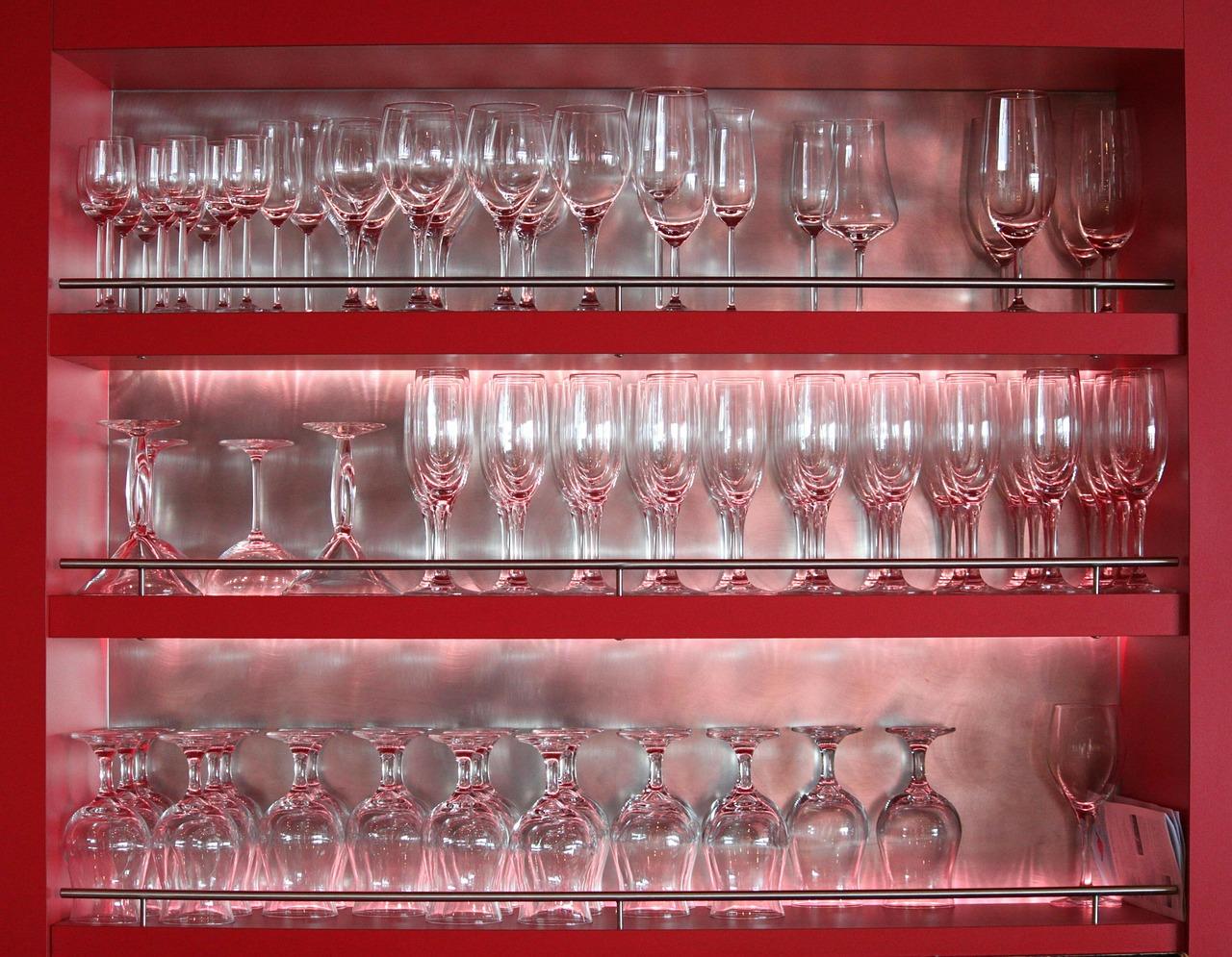 Ein Gläserschrank mit roten Fächern und indirekter Vitrinenbeleuchtung