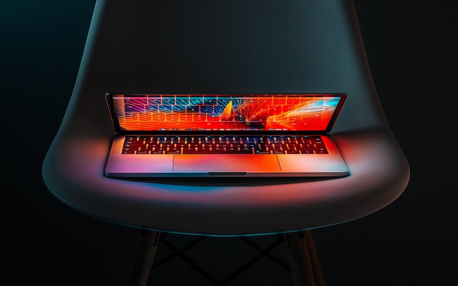 Ein Laptop auf einem Stuhl, der Dank OLEDs magisch in strahlenden Farben leuchtet.